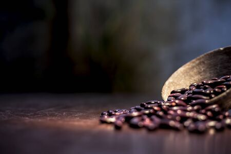 Close up of raw kidney beans on brown colored surface in a clay bowl with a spotlight on it. Horizontal shot.