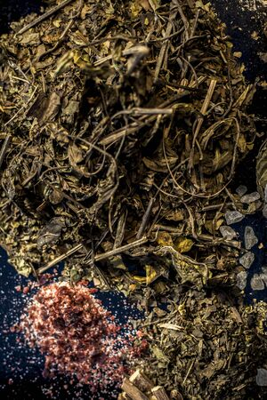 Best home ayurvedic remedy for ulcer i.e. Ardusi or Malabar nut, sugar, and mulethi or licorice. Shot of all the herbs on black surface with powder also. Фото со стока