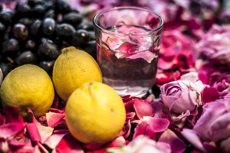 Face mask or solution to excessively oily skin on blackboard consisting of some grape pulp well mixed with lemon juice. Shot of grapefruit with some red and pink rose and lemons.