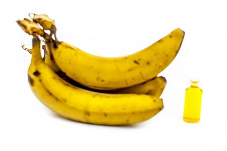 Close up shot of banana oil in a glass bottle or isoamyl acetate along with fresh yellow bananas isolated on white.