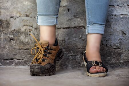The elegant foot of young teenage girl wearing peep-toe sandals in one foot and hiking boots in another posing against a brick wall wearing blue denim jeans. Stock Photo