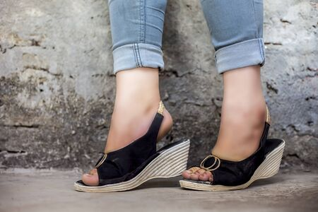 Close up shot of female foot wearing stylish white and black colored sandals and blue jeans posing against a brick wall.