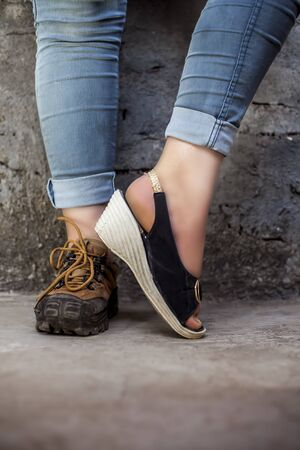 Female foot wearing hiking boots in one foot and sandals in another and posing against a brick wall wearing jeans.