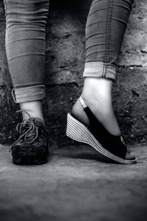 The elegant foot of young teen girl wearing peep-toe sandals in one foot and hiking boots in another posing against a brick wall wearing blue denim jeans.Vertical shot in black and white colors.