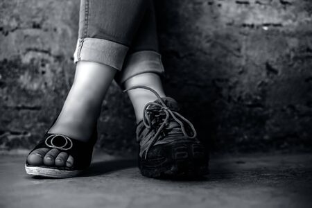 The elegant foot of young teen girl wearing peep-toe sandals in one foot and hiking boots in another posing against a brick wall wearing blue denim jeans.Horizontal shot in black and white colors.