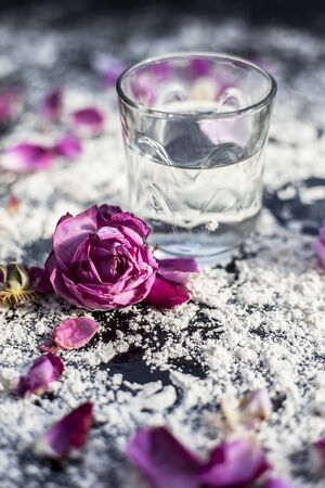 Close up shot of a glass of water along with some rose petals on a black board spread with some wheat flour. Concept of face mask applied in spa and cosmetic centre.