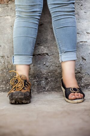 The elegant foot of young teen girl wearing peep-toe sandals in one foot and hiking boots in another posing against a brick wall wearing blue denim jeans. Vertical shot.