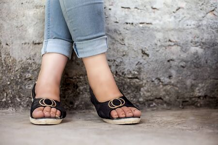 Close up shot of female legs wearing blue washed skinny fit denim jeans and black and white peep toe high heel sandals matching jeans and posing against a rough brick wall. Stock Photo