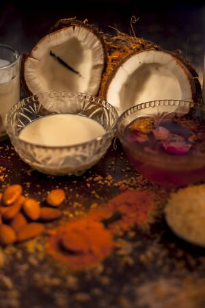 Complete face mask of coconut, consisting of coconut milk, rose water, yogurt, buttermilk, oatmeal, almonds, lime juice, turmeric, rice flour, honey, olive oil, and sandalwood powder. Vertical shot.