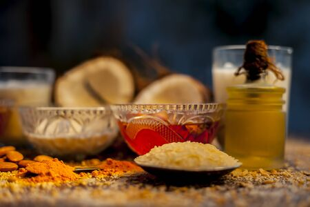 Complete face mask of coconut, consisting of coconut milk, rose water, yogurt, buttermilk, oatmeal, almonds, lime juice, turmeric, rice flour, honey, olive oil, and sandalwood powder. Horizontal shot.