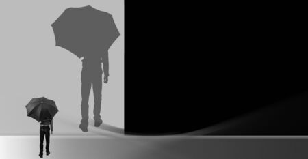 Creative minimalistic shot of a man standing holding a black umbrella and looking towards his enlarged magnified shadow on a creative wall. Horizontal shot in black and white colors.
