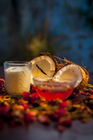 Coconut face mask consisting of coconut milk and yogurt for flawless skin and to moisturize it. Shot of raw coconut cut coconut, milk, and yogurt with some flowers spread on the brown wooden surface.