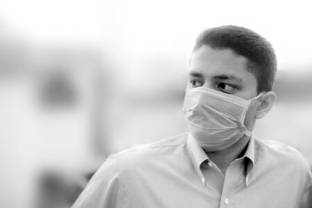 Portrait shot of a young man in blue colored shirt and wearing a surgical mask or a procedure mask with blurred background. Фото со стока