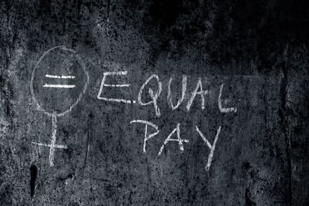 Creative representation of Equal pay with a bigender symbol over a rough wall with written Equal pay.