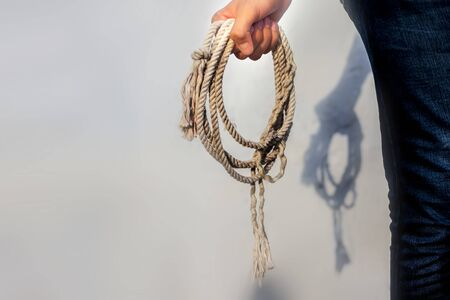 Close up shot of male holding a lasso or cowboy rope in his hands against a white wall.
