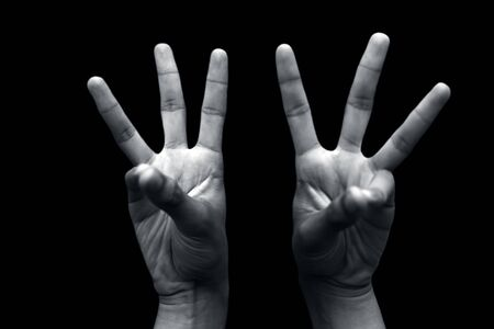 Pair of hands demonstrating Bhudi Yoga Mudra isolated over a black colored background. Stock Photo
