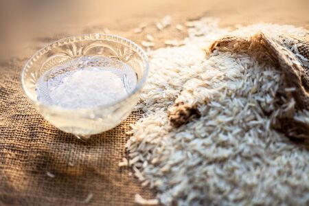 Shot of rice water in glass bowl with gunny bag full of basmati white rice in it over a brown surface.