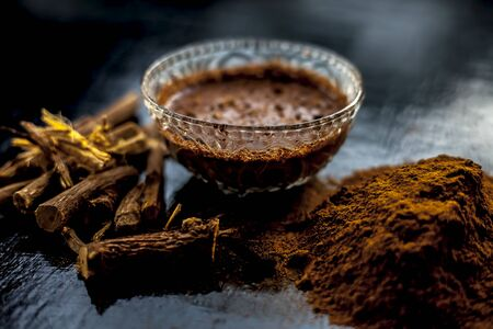 Close up shot of fresh raw revand chini roots and its paste in a glass bowl along with some raw powder on a wooden black surface. Foto de archivo