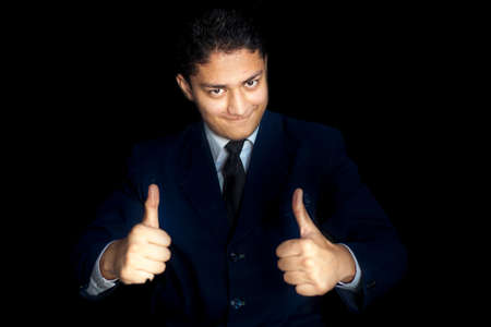 Portrait shot of smiling charming young businessman in dark blue shirt and Wishing Best Wishing Good luck with thumbs up Or Best of luck hand gesture over a black colored background. Horizontal shot. Banque d'images