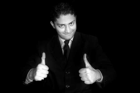 Portrait shot of smiling charming young businessman in dark blue shirt and Wishing Best Wishing Good luck with thumbs up Or Best of luck hand gesture over a black colored background. Horizontal shot. 免版税图像