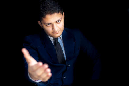 Shot of a businessman giving hand to collaborate in front of camera isolated on a black colored background. Shot of a worker in a blue suit trying to collaborate isolated.