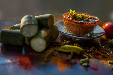 Close up shot of Gujarati famous Galka Nu Shaak on a glass plate. Shot of sponge gourd dish in a glass plate along with all the spices on a brown with some fresh tomatoes and sponge gourd. Banque d'images
