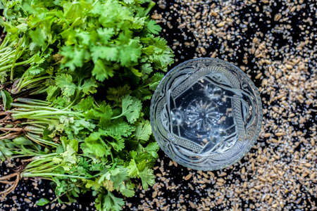 Exfoliating skincare face mask on a black colored surface consisting of some coriander leaves and egg white along with some oats. 免版税图像