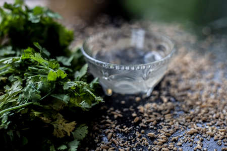 Exfoliating skincare face mask on a black colored surface consisting of some coriander leaves and egg white along with some oats. Banque d'images