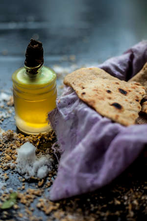 Shot of bhakri in a basket container along with some wheat flour spread on the surface and some cooking oil in a small glass bottle on a black colored surface. close up shot of traditional Gujarati bread Bhakri. 免版税图像