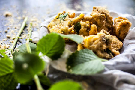 Close up shot of monsoon snack ajwain pakora in a container along with some fresh ajwain leaf with it on a surface with some sprinkled chickpea flour with all the ingredients required to make pakora.