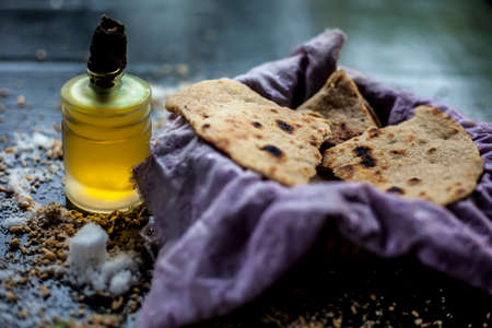 Shot of bhakri in a basket container along with some wheat flour spread on the surface and some cooking oil in a small glass bottle on a black colored surface. close up shot of traditional Gujarati bread Bhakri. Banque d'images