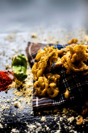 Famous Kanda bhaji or Kanda bhajiya or Kanda pakora in a container on a black surface along with chickpea flour, spices, onion, and all other ingredients for making it. Horizontal shot.
