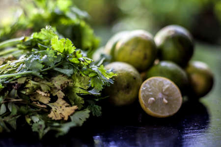 Face mask for blackhead and dry skin on a surface consisting of some coriander leaves and fresh lemon juice. Shot of fresh parsley leaves and lemons for blackhead removal face mask.