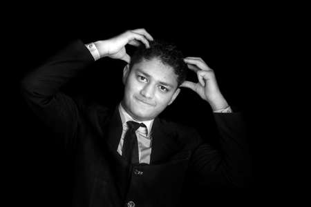 Frustrated man holding his head with tension and posing on a black colored background wearing a  blue colored suit.