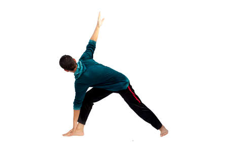 Full-length shot of male teenager practicing Revolved Yoga Pose or Revolved Triangle Yoga Pose or Parivrtta Trikonasana isolated on white background. 免版税图像 - 159371202