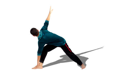 Full-length shot of male teenager practicing Revolved Yoga Pose or Revolved Triangle Yoga Pose or Parivrtta Trikonasana isolated on white background.