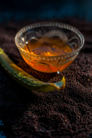 Mustard seed face mask for glowing skin. Shot of face mask ingredients which are mustard seeds, aloe vera, and some honey in a glass bowl on a black surface. 免版税图像 - 159233646