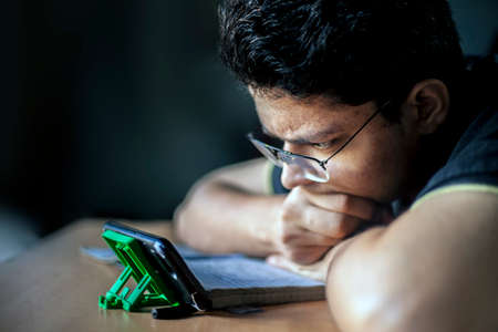 Close portrait shot of a male teenager watching something interesting on his phone.