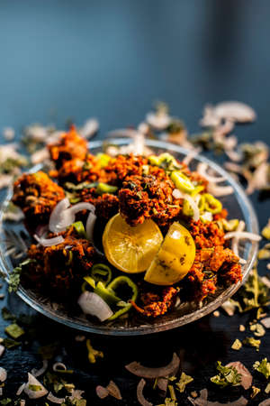 Indian styled meatballs or kabab or kebab on glass plate along with sprinkled cut green chilies and onion rings plus lemon.