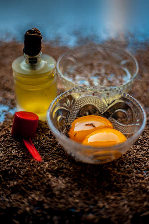 Hair mask for healthy long hair consisting of cumin seeds or zeera or jeera along with some raw egg yolk, water and some olive oil on a brown colored wooden surface. 版權商用圖片