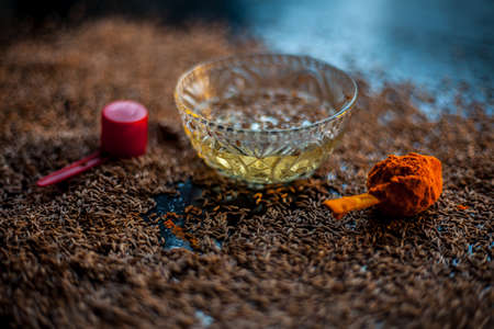 DIY Face mask for smooth and glowing skin. Shot of cumin seeds along with some turmeric on a brown surface making a glowing skin face mask all together.