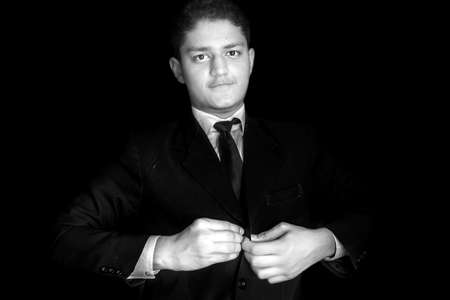 Portrait shot of a businessman adjusting his tie before a meeting isolated on black background.