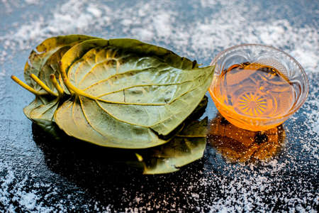 Face mask for controlling oiliness consisting of betel leaves juice, honey, sea-salt on a black wooden surface.