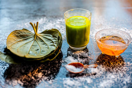 Face mask for preventing acne on a black wooden surface of betel leaves and turmeric powder.