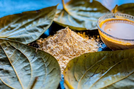 Face mask for nourishing your skin consisting of betel leaves, besan or chickpea powder, Multani mitti, or mulpani mitti on a black surface.