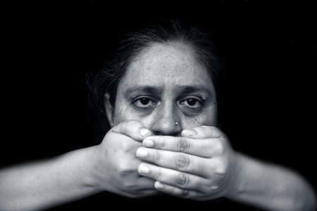 Modern creative shot of a lady with hands closing her lips and expressing speak no evil isolated on black background in black and white colors.