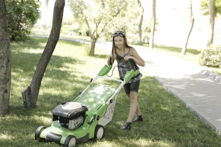 Girl with lawn mower Stock Photo - 21164025