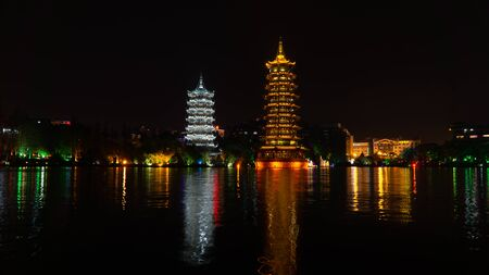 The Sun and Moon Twin Pagodas during evening. View of Shanhu Lake (Fir Lake) in downtown of Guilin, China