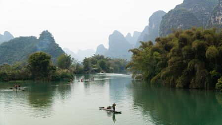 Traditional bamboo rafting along Yulong river, famous limestone hills on the banks of river, China