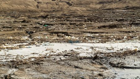 Dirty and muddy coastline of famous Dead Sea, a lot of garbage around Dead Sea, extremely salt lake, Jordan Stock Photo